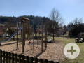 Spielplatz mit Klettergerüst, Rutsche, Karussell, Kletterwand und einem Unterstand.