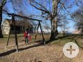 Spielplatz mit Schaukel, Rutsche, Kletterwand und Karussell.