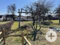Spielplatz mit einer Schaukel, Rutsche, Karussell, Wippe, Klettergerüst, Seilbahn und einem Sandkasten.