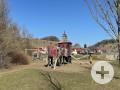 Spielplatz  mit einem roten Kletterturm und einer Rutsche, im Hintergrund eine Schaukel vor einer Häusersiedlung.