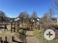 Ein Spielplatz mit einer Kletterbrücke mit rotem Netz, auf der rechten Seite sind Holzpfähle zum Klettern