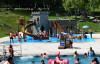Blick vom großen Becken auf den Wasserspielplatz. mit Besuchern.